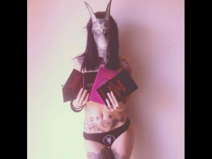 Satanic Woman Holds Book of Satanic Magic by Aleister Nacht